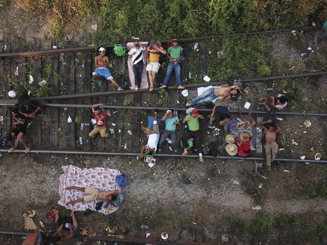 Migrants, who are part of a caravan of Central American migrants slowly makes its way toward the U.S. border, rest on the rails in Arriaga, Mexico, Friday, Oct. 26, 2018. Many migrants said they f ...
