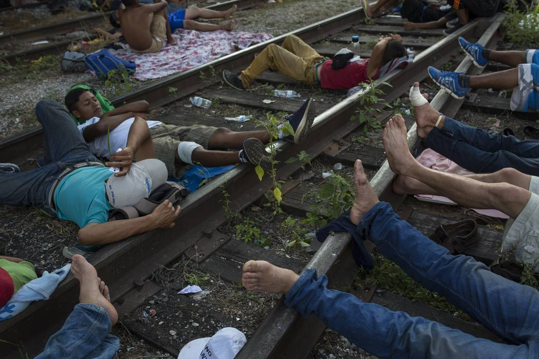 Migrants rest on the railroad rails, as a thousands-strong caravan of Central American migrants slowly makes its way toward the U.S. border, between Pijijiapan and Arriaga, Mexico, Friday, Oct. 26 ...