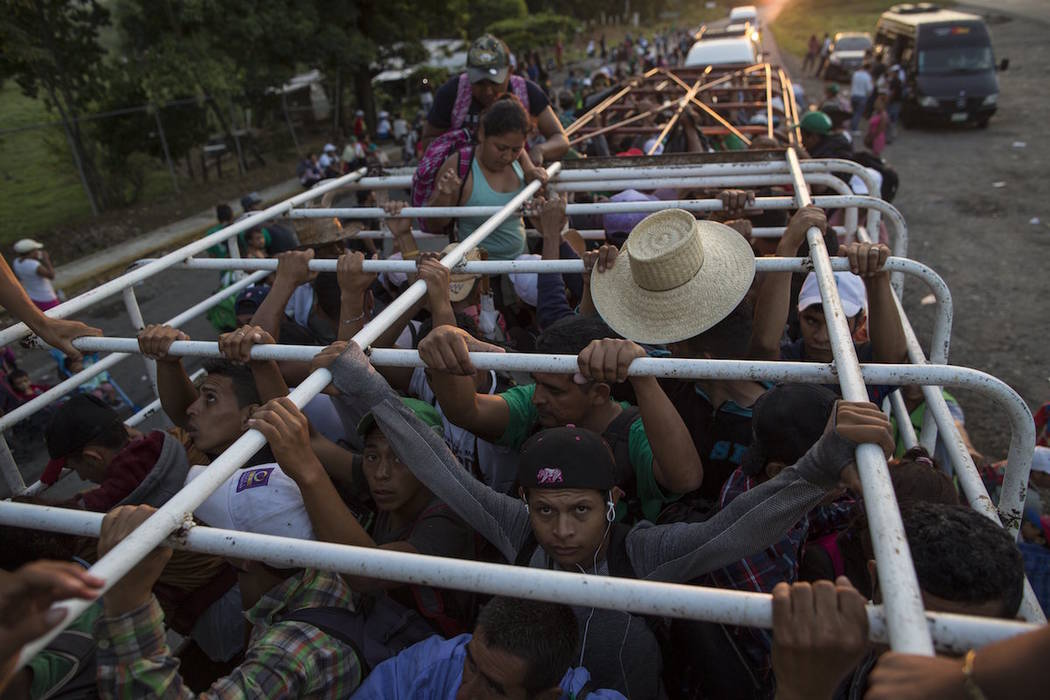 Migrants travel on a cattle truck, as a thousands-strong caravan of Central American migrants slowly makes its way toward the U.S. border, between Pijijiapan and Arriaga, Mexico, Friday, Oct. 26, ...