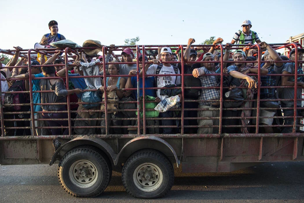 Migrants ride in a cattle truck, as a thousands-strong caravan of Central American migrants slowly makes its way toward the U.S. border, between Pijijiapan and Arriaga, Mexico, Friday, Oct. 26, 20 ...