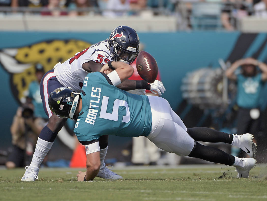 Jacksonville Jaguars quarterback Blake Bortles (5) fumbles the ball as he is hit by Houston Texans linebacker Whitney Mercilus, top, during the first half of an NFL football game, Sunday, Oct. 21, ...