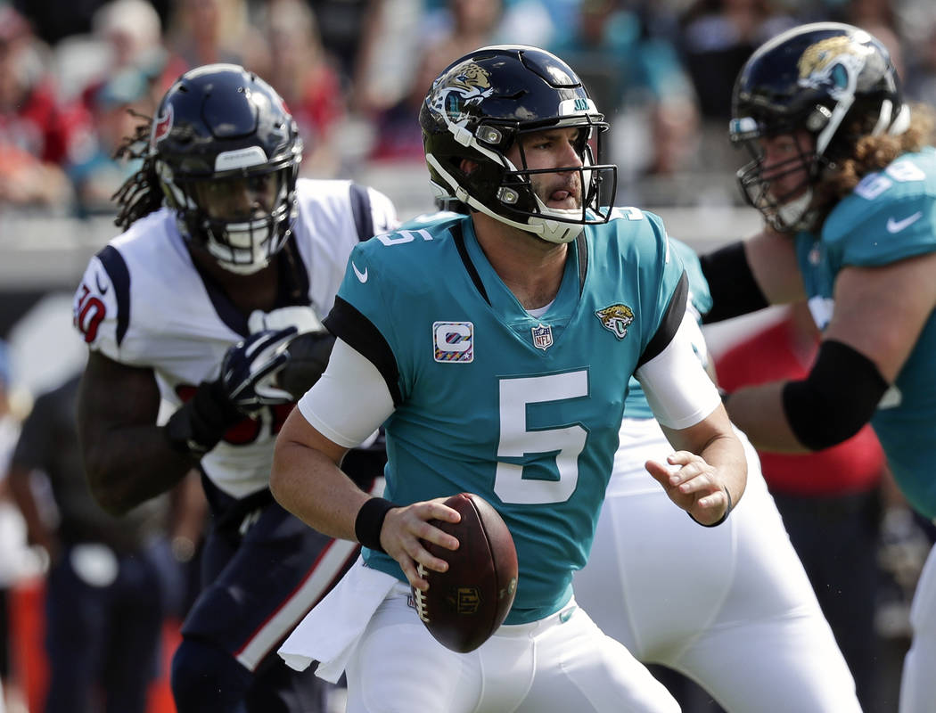 FILE - In this Sunday, Oct. 21, 2018, file photo, Blake Bortles (5) looks for a receiver as he is pressured by Houston Texans linebacker Jadeveon Clowney, back left, during the first half of an NF ...