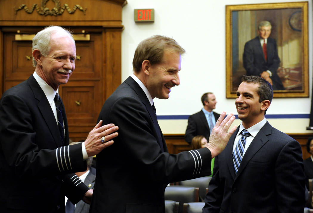 In this Feb. 24, 2009, file photo, Air Traffic Control Specialist Patrick Harten, right, smiles as US Airways flight 1549 Capt. Chesley B Sullenberger III, right, and First Officer Jeffrey B. Skil ...
