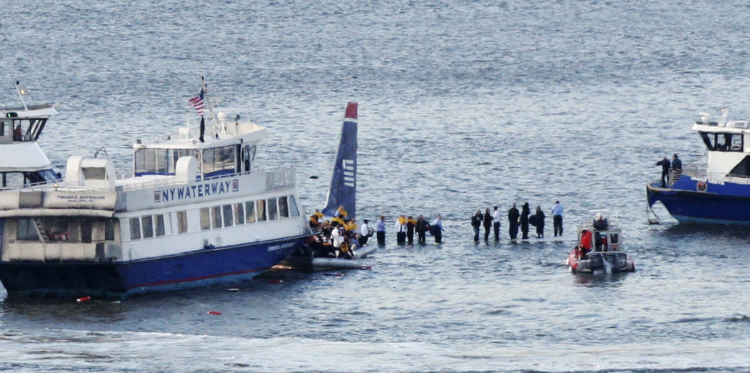FILE - In this Jan. 15, 2009, file photo, ferry boats surround a US Airways aircraft that went down in the Hudson River in New York as passengers stand on the wings of a US Airways jetliner on the ...