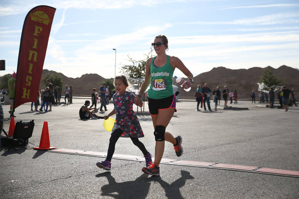 Shae Deschutter of Henderson runs to the finish line with her daughter Brighton, 5, during the Halloween half marathon run at Fiesta Henderson hotel-casino in Las Vegas, Saturday, Oct. 27, 2018. E ...