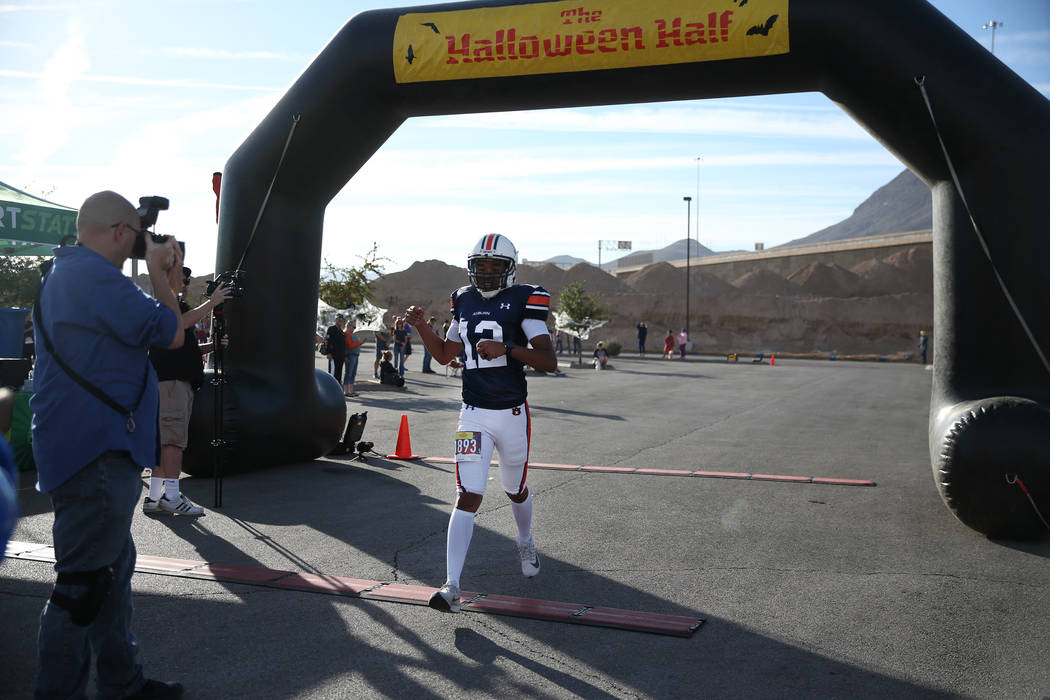 Paul Naylor, 33, of Las Vegas, runs across the finish line in his Guinness World Records attempt to get the fastest half marathon wearing football gear, during the Halloween half marathon run at F ...