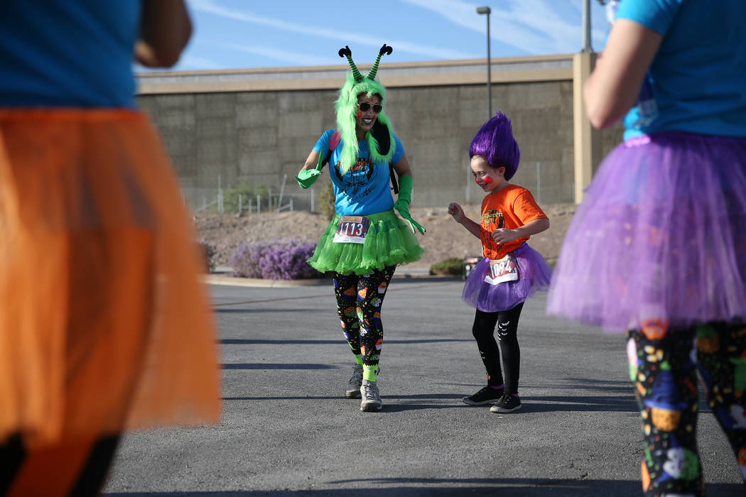 Tracey Fabre, left, with her niece Ashely Del Rial, 6, dance to the music before the starts of the Halloween 5K run at Fiesta Henderson hotel-casino in Las Vegas, Saturday, Oct. 27, 2018. Erik Ver ...