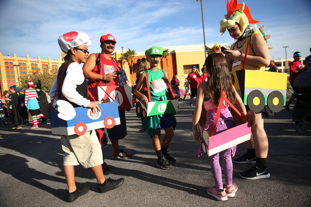 Mark Bagaoisan, from left, with family members Randy Ramos, his son Rome, 10, daughter London, 8, and wife Larissa, before the Halloween 5K run at Fiesta Henderson hotel-casino in Las Vegas, Satu ...