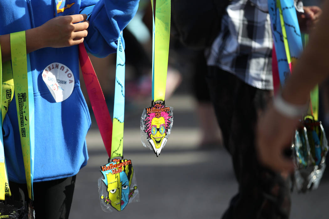 Medals are given out to finishers of the Halloween 5K run at Fiesta Henderson hotel-casino in Las Vegas, Saturday, Oct. 27, 2018. Erik Verduzco Las Vegas Review-Journal @Erik_Verduzco