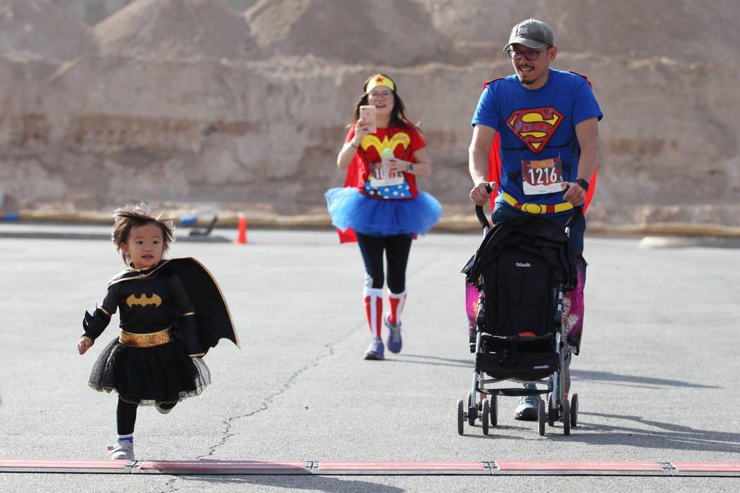 Maya Lim, 2, from left, sprints to the finish with her parents Olivia Chao and Seng Lim, during the Halloween 5K run at Fiesta Henderson hotel-casino in Las Vegas, Saturday, Oct. 27, 2018. Erik Ve ...