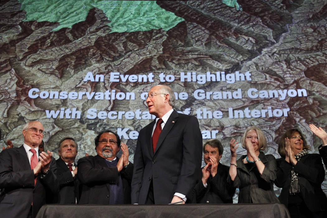 Then Interior Secretary Ken Salazar, center, standing in front of a map of the Grand Canyon, is applauded after announcing a 20 year ban on new mining claims near the Grand Canyon in Washington on ...