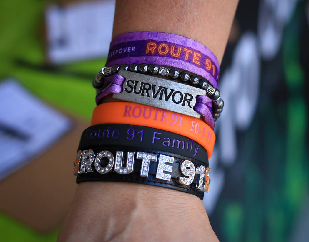 Kimberly Dalrymple, 47, displays her Route 91 bracelets at the Country 58 Benefit Concert at the Henderson Pavilion on Saturday, Oct. 27, 2018. The two purple cloth bracelets are from the festival ...