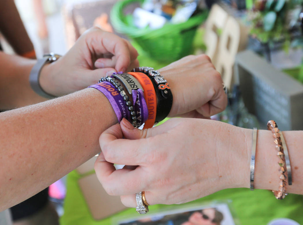 Kimberly Dalrymple, 47, left, shows her Route 91 bracelets to Janny Copeland, 36, right, at the Country 58 Benefit Concert at the Henderson Pavilion on Saturday, Oct. 27, 2018. The two purple clot ...