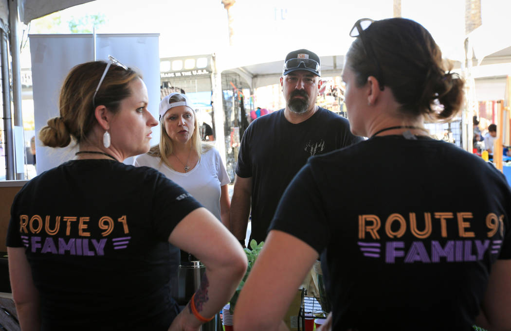 Lauren Atkins, 34, right, and Janny Copeland, 36, left, share their Route 91 survival stories with Kimberly Dalrymple, 47, center left, and her husband Anthony Dalrymple, 45, center right, who are ...