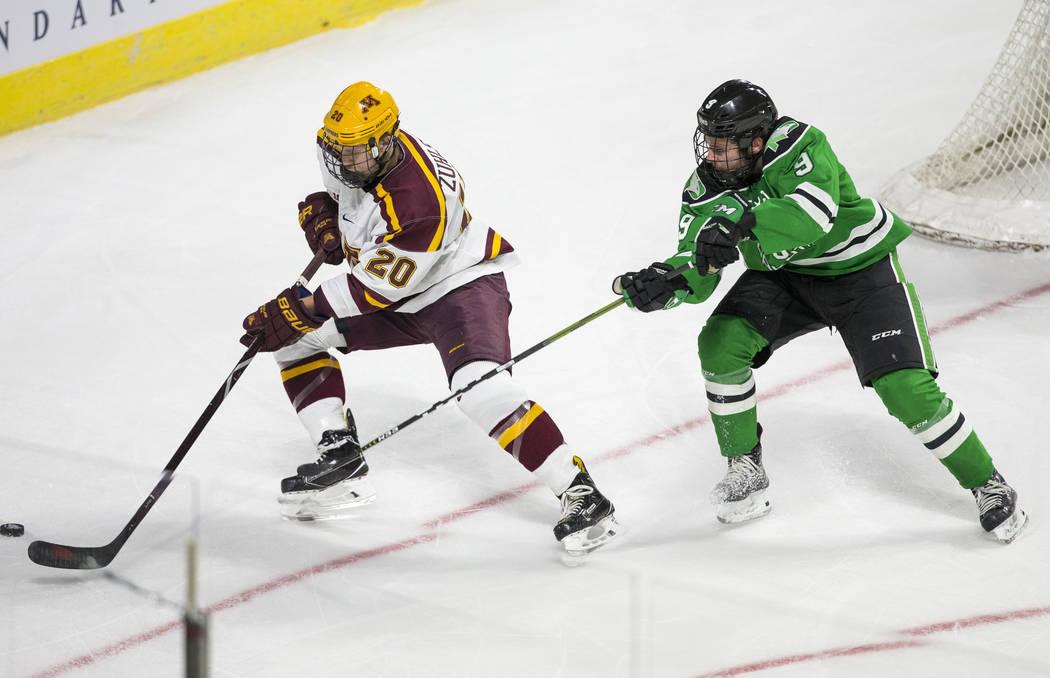 Minnesota Golden Gophers defenseman Ryan Zuhlsdorf (20) controls the puck as North Dakota Fighting Hawks forward Dixon Bowen (9) defends during the second period of the U.S. Hockey Hall of Fame Ga ...