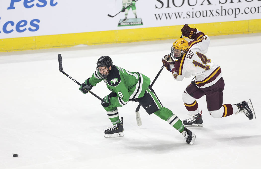 North Dakota Fighting Hawks forward Nick Jones (8) and Minnesota Golden Gophers forward Garrett Wait (14) vie for the puck during the second period of the U.S. Hockey Hall of Fame Game at the Orle ...
