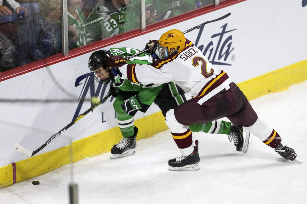 North Dakota Fighting Hawks forward Mark Senden (19) gets checked by Minnesota Golden Gophers defenseman Jack Sadek (2) during the second period of the U.S. Hockey Hall of Fame Game at the Orleans ...