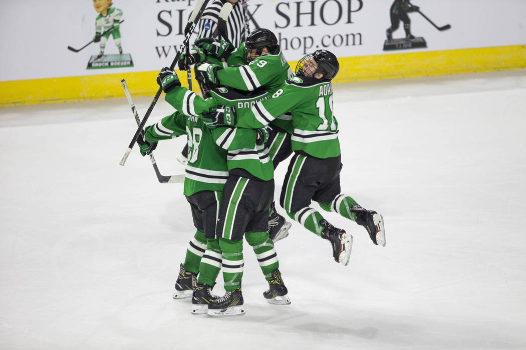 The North Dakota Fighting Hawks celebrate a third period goal by defenseman Colton Poolman (6) during the U.S. Hockey Hall of Fame Game against Minnesota Golden Gophers at the Orleans Arena in Las ...