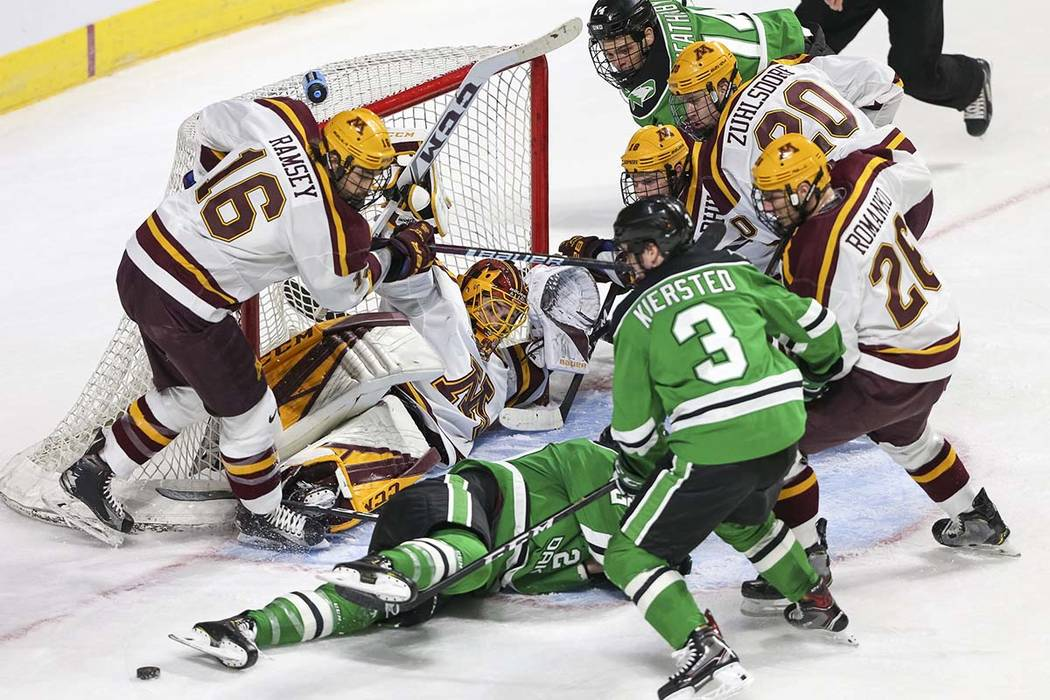 Minnesota Golden Gophers goaltender Mat Robson (40) defends his goal on his back as North Dakota Fighting Hawks players looks for the rebound during the second period of the U.S. Hockey Hall of Fa ...