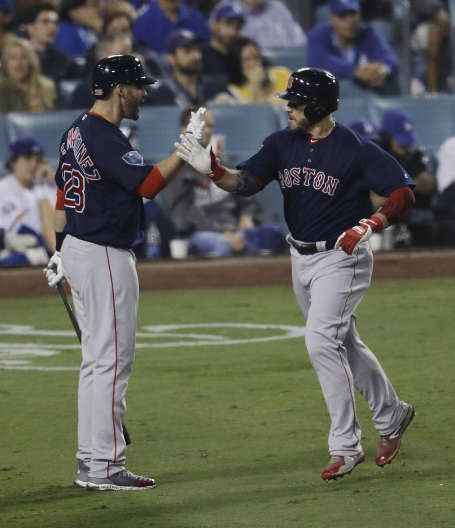 Boston Red Sox's Steve Pearce celebrates his solo home run to tie the game with J.D. Martinez during the eighth inning in Game 4 of the World Series baseball game against the Los Angeles Dodgers o ...
