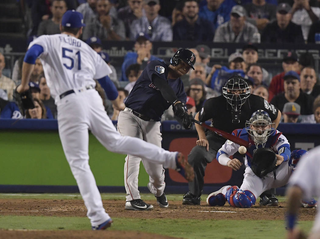 Boston Red Sox's Rafael Devers hits a RBI-single off Los Angeles Dodgers relief pitcher Dylan Floro during the ninth inning in Game 4 of the World Series baseball game on Saturday, Oct. 27, 2018, ...