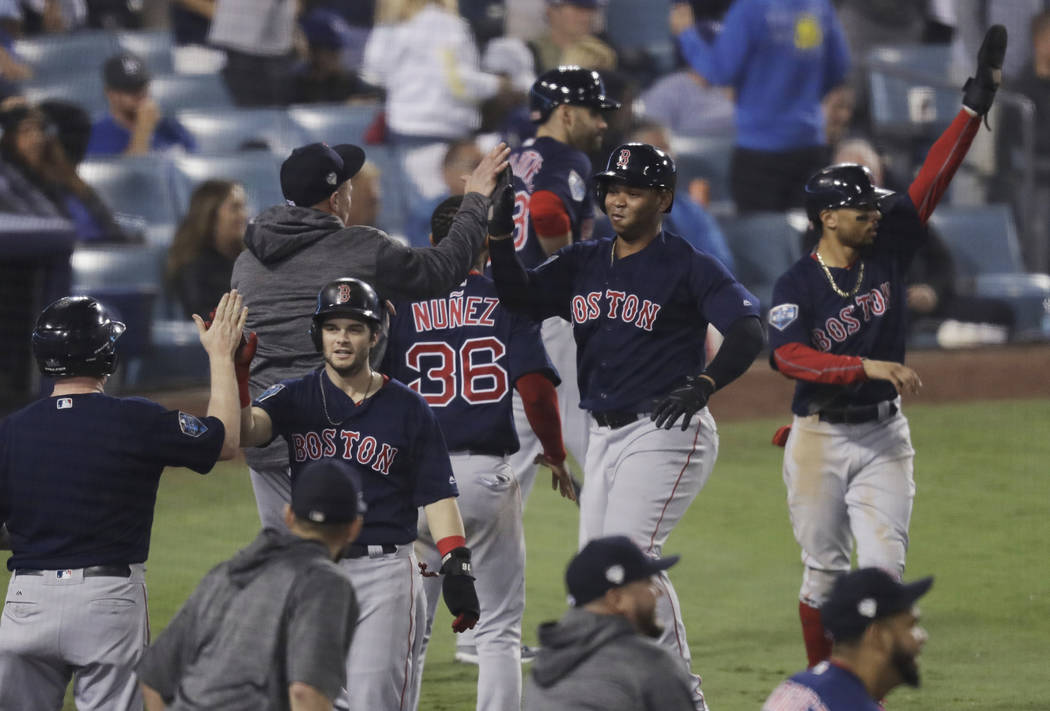 From left, Boston Red Sox's Andrew Benintendi, Rafael Devers and Mookie Betts celebrate after scoring on a three-run RBI double by Steve Pearce during the ninth inning in Game 4 of the World Serie ...