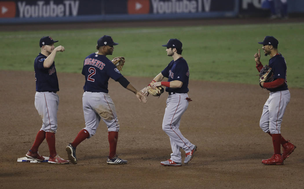 From left, Boston Red Sox's Brock Holt, Xander Bogaerts, Andrew Benintendi and Mookie Betts celebrate after Game 4 of the World Series baseball game against the Los Angeles Dodgers on Saturday, Oc ...