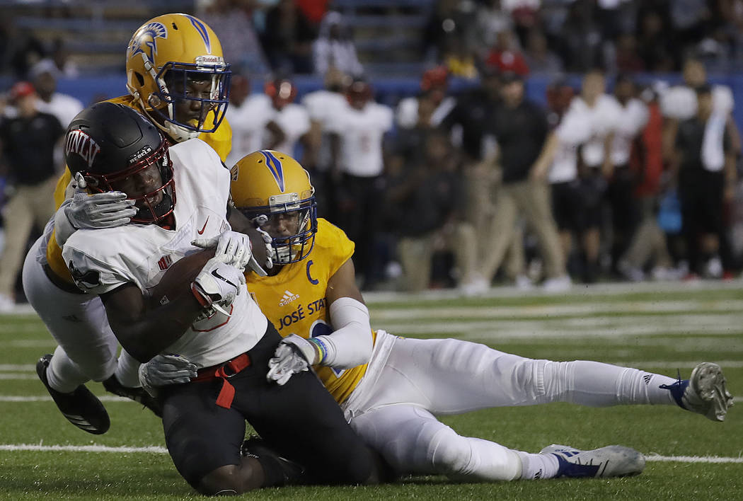 UNLV wide receiver Tyleek Collins, foreground, is tackled by San Jose State cornerback Dakari Monroe, right, and safety Jonathan Lenard Jr. during the second half of an NCAA college football game ...