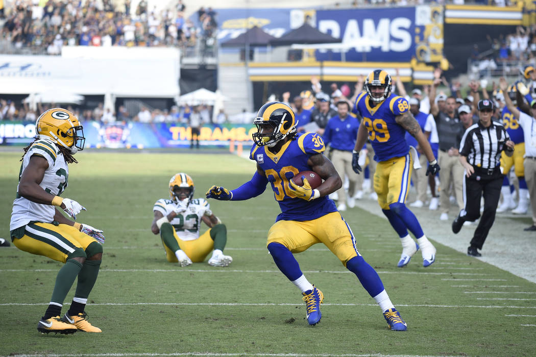 Los Angeles Rams running back Todd Gurley turns away from the end zone before being tackled by Green Bay Packers cornerback Tramon Williams, left, during the second half of an NFL football game, S ...