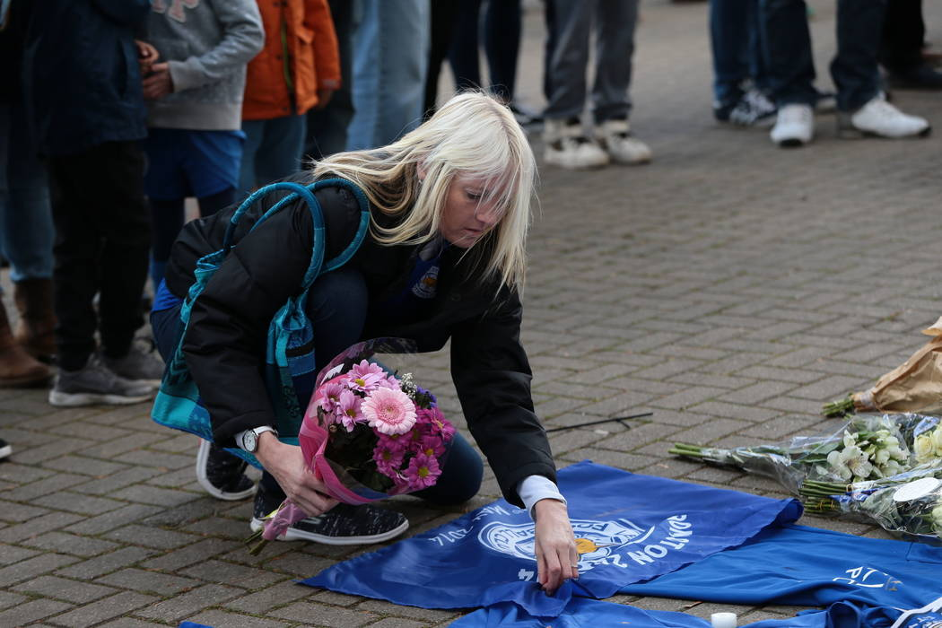 A woman places flowers outside Leicester City Football Club after a helicopter crashed in flames the day before, in Leicester, England, Sunday, Oct. 28, 2018. A helicopter belonging to Leicester C ...