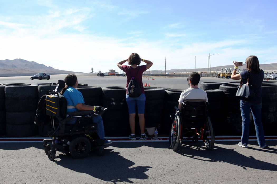 Spectators watch the raceway at an event for Driven, a new rehabilitation center to help people with disabilities that will be built in downtown Las Vegas at SpeedVegas in Las Vegas, Sunday, Oct. ...