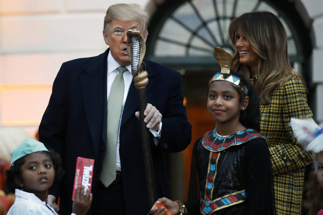 President Donald Trump holds up part of a child's halloween costume as he and first lady Melania Trump give candy to children during a Halloween trick-or-treat event at the White House, Sunday, Oc ...
