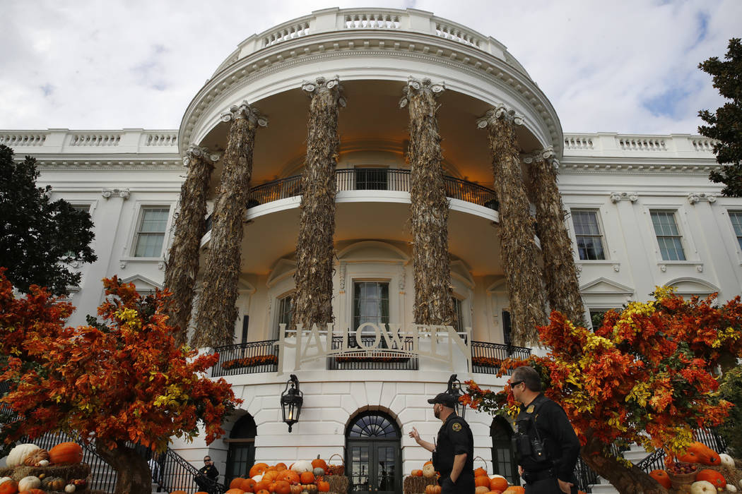 Secret Service police walk past the South Portico of the White House decorated for Halloween, Sunday, Oct. 28, 2018, in Washington. President Donald Trump and first lady Melania Trump will greet c ...