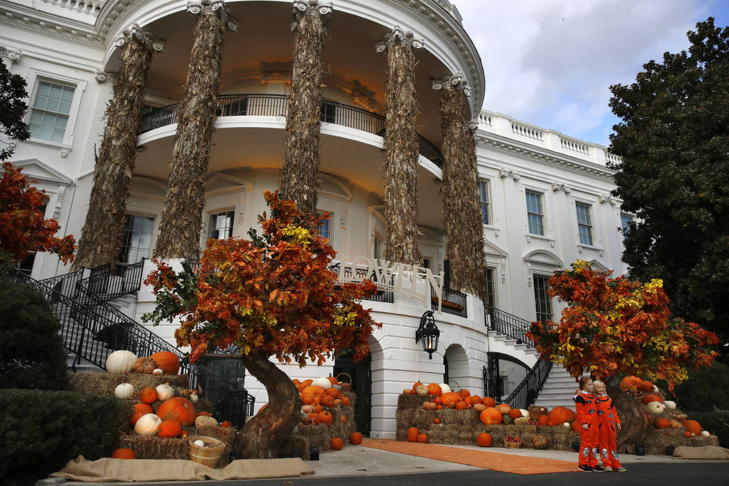 Two girls pose for a photograph with the decorated South Portico of the White House, Sunday, Oct. 28, 2018, in Washington, ahead of a Halloween event with President Donald Trump and first lady Mel ...