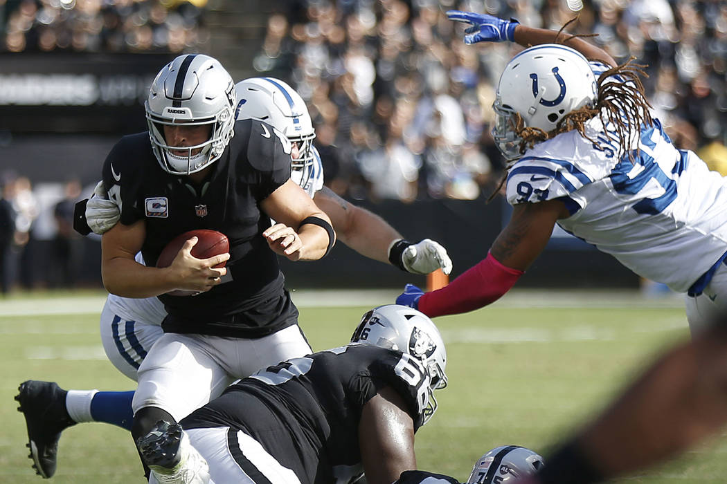 Oakland Raiders quarterback Derek Carr, foreground left, scrambles away from Indianapolis Colts defenders during the second half of an NFL football game in Oakland, Calif., Sunday, Oct. 28, 2018. ...