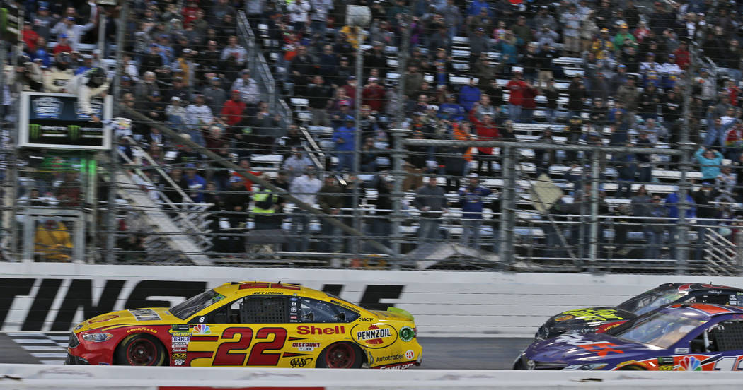 Joey Logano (22) crosses the finish line followed by Denny Hamlin (11) and Martin Truex Jr. (78) to win the Monster Energy NASCAR Cup Series auto race at Martinsville Speedway in Martinsville, Va. ...
