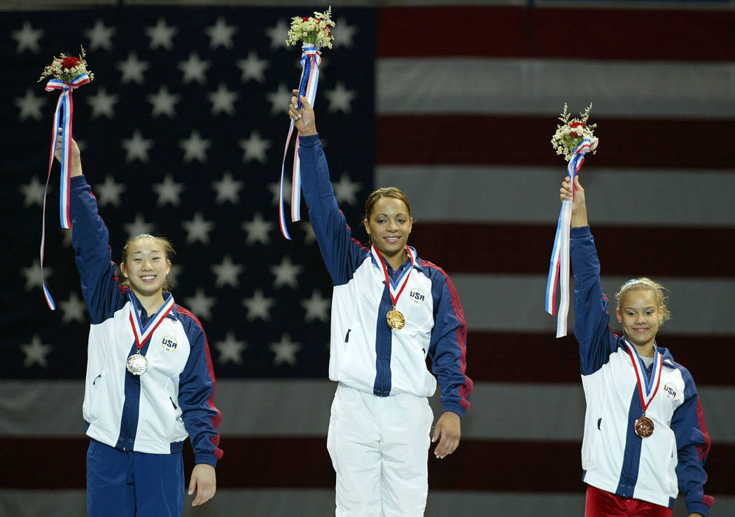 Tasha Schwikert, center, takes home the gold medal, Tabitha Yim, left, takes home the silver medal and Ashley Postell, right, takes home the bronze medal at the US Gymnastics championships at Gund ...