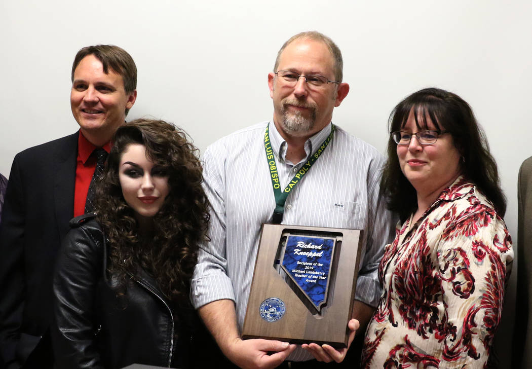 Richard Knoeppel, second right, an architectural design instructor at Advanced Technologies Academy, poses for a photo with Principal Jonathan Synold, left, his daughter Erin, second left, and his ...