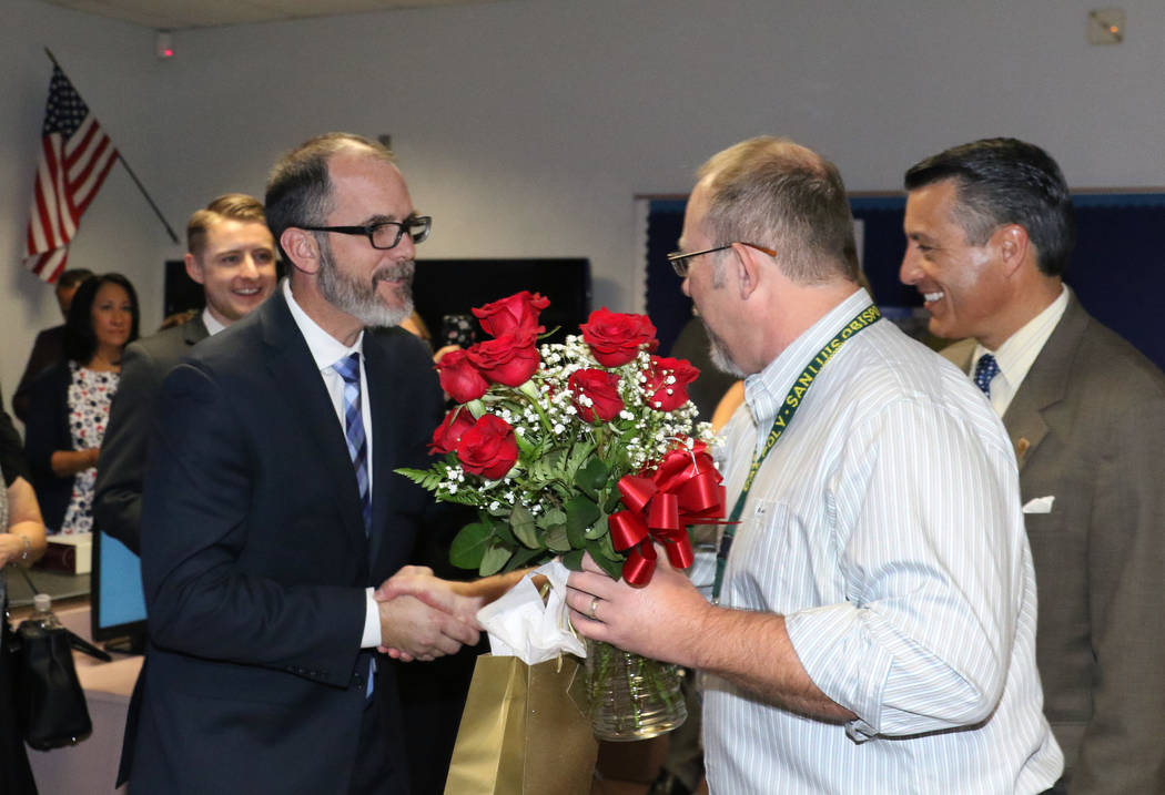 Richard Knoeppel, center, an architectural design instructor at Advanced Technologies Academy, is congratulated by Steve Canavero, superintendent of public instruction for the Nevada Department of ...