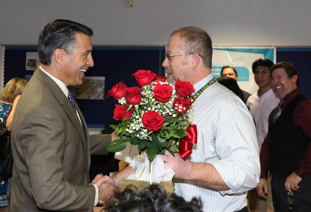 Richard Knoeppel, right, an architectural design instructor at Advanced Technologies Academy, is congratulated by Gov. Brian Sandoval after being named the 2018 Nevada Teacher of the Year on Monda ...