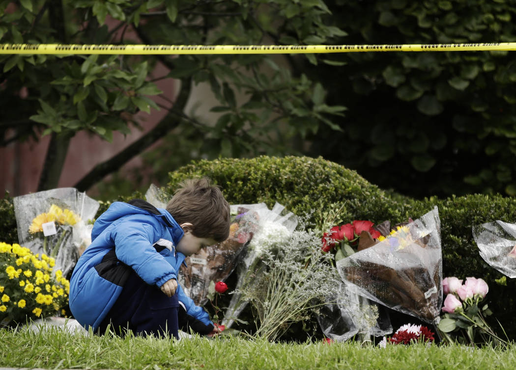 Gideon Murphy places a flower at the Tree of Life Synagogue in Pittsburgh, Sunday, Oct. 28, 2018. Robert Bowers, the suspect in Saturday's mass shooting at the synagogue, expressed hatred of Jews ...