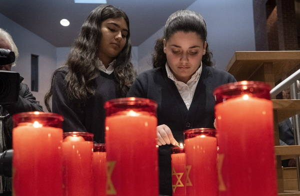 Candles are lit, one for each of the 11 victims, during a Montreal Jewish Community memorial vigil for the victims of the Pittsburgh synagogue attack, in Montreal on Monday, Oct. 29, 2018. (Paul C ...