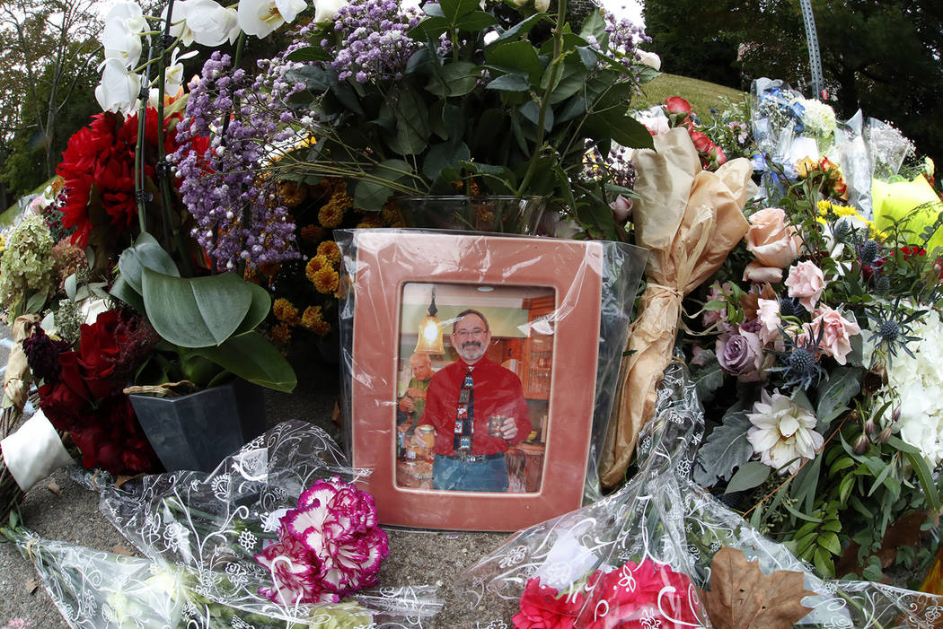 A photo of Tree of Life Synagogue victim Dr. Jerry P. Rabinowitz is surrounded Monday, Oct. 29, 2018, by flowers, part of a spontaneous memorial of flowers that has grown a block from the temple w ...