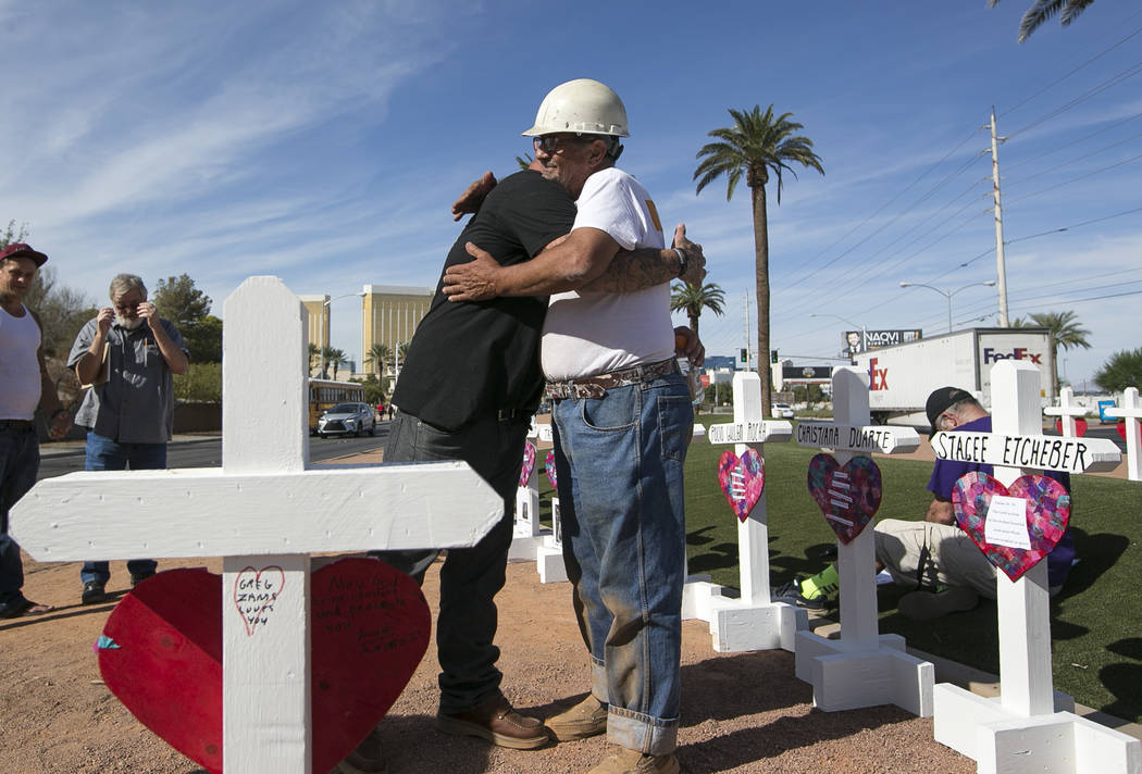 Cross maker Greg Zanis, right, gets a hug from Mike Warino, brother of Oct.1 shooting victim Heather Alvarado, near the Welcome to Fabulous Las Vegas sign on Friday, Sept. 28, 2018. Zanis gave War ...