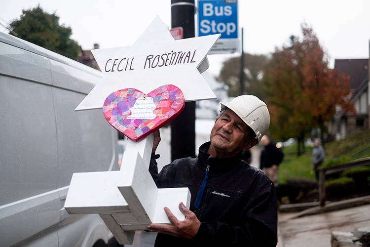 Greg Zanis carries a wooden marker with the name Cecil Rosenthal on it. After the tragic shooting in Pittsburgh, PA at the Tree of Life. Community gathers from all different races and religions. ...