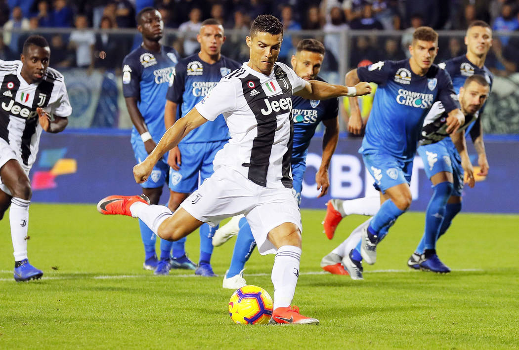 Juventus' Cristiano Ronaldo scores on a penalty his side's opening goal, during the Serie A soccer match between Empoli and Juventus at the Carlo Castellani stadium in Empoli, Italy, Saturday, Oct ...