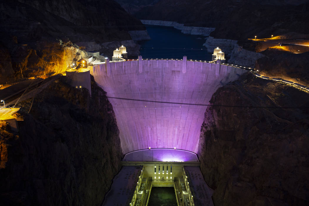 As seen from the Mike O'Callaghan-Pat Tillman Memorial Bridge, the Hoover Dam is lit up with purple to recognize Domestic Violence Awareness Month on Monday, Oct. 29, 2018. Caroline Brehman/Las Ve ...