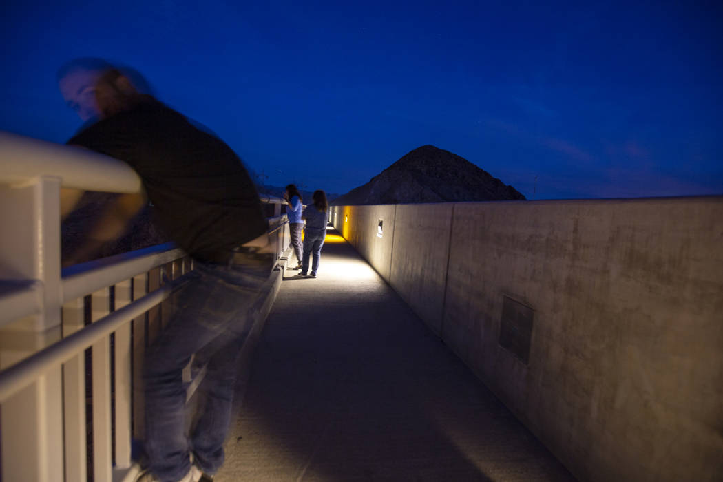 People gathered on the Mike O'Callaghan-Pat Tillman Memorial Bridge view the Hoover Dam as it is lit up with purple to recognize Domestic Violence Awareness Month on Monday, Oct. 29, 2018. Carolin ...