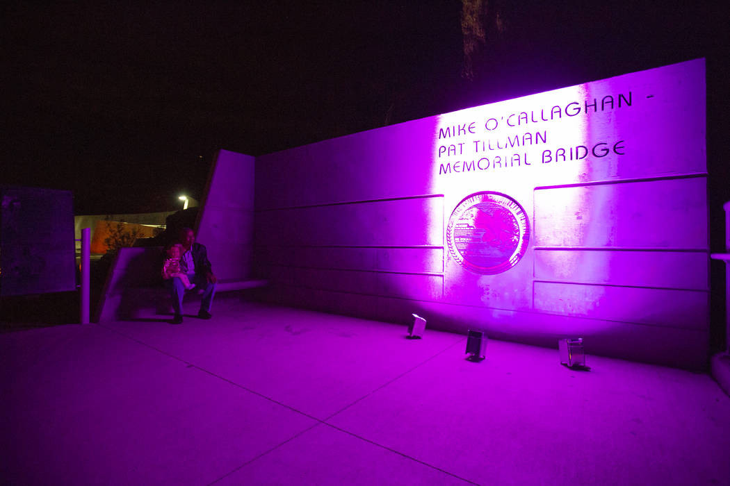 People gather near the Mike O'Callaghan-Pat Tillman Memorial Bridge as the Hoover Dam is lit up with purple to recognize Domestic Violence Awareness Month on Monday, Oct. 29, 2018. Caroline Brehma ...