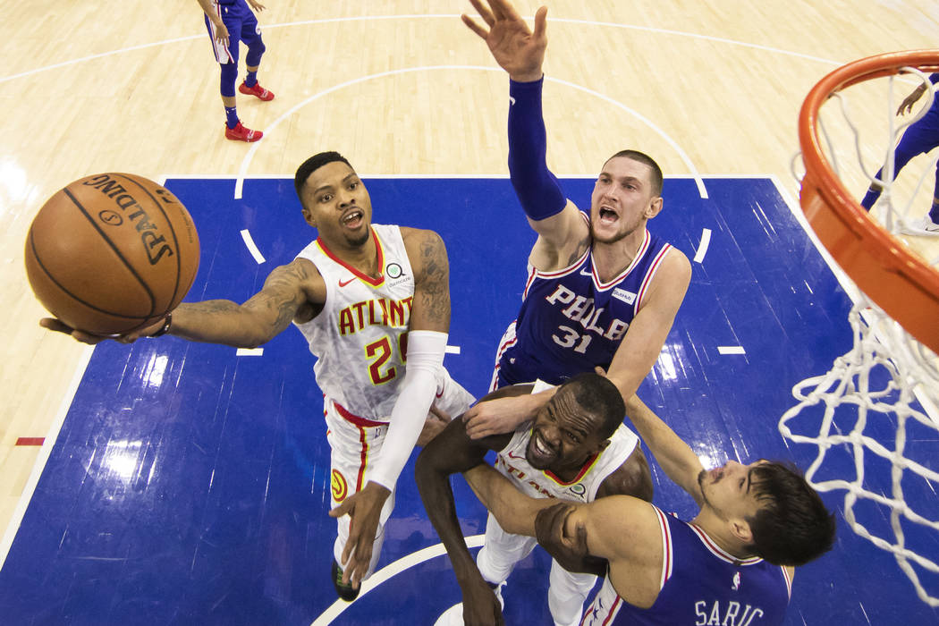 Atlanta Hawks' Kent Bazemore, left, puts up the shot as Philadelphia 76ers' Mike Muscala (31) goes over Atlanta Hawks' Dewayne Dedmon, center left, to try to defend during the second half of an NB ...